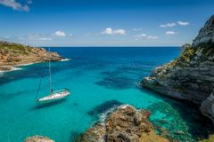 Dreamy bay seascape. Dream bay seascape with turquoise transparent water and sailing boat. Mallorca island, Spain Stock Images
