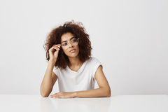 Dreamy beautiful african girl in glasses thinking over white background. Copy space. Dreamy young beautiful african girl in glasses thinking over white Royalty Free Stock Images