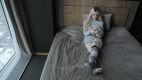 Dreamy Beautiful blonde woman sitting on the bed with smart phone. Girl smiles, good mood. Blogging, browsing internet. Chatting. In a warm cozy sweater and stock footage