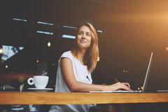 Dreamy beautiful female using portable net-book during work break in coffee shop royalty free stock images