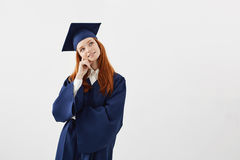 Dreamy beautiful girl graduate thinking dreaming over white background.Copy space. Dreamy beautiful girl in mantle graduate thinking dreaming over white Royalty Free Stock Image