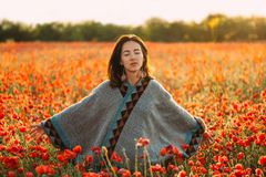 Dreamy beautiful woman relaxing in red poppy meadow. Boho stylish dreamy beautiful young woman relaxing with closed eyes in red poppy flower meadow in summer stock images
