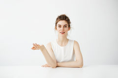 Dreamy beautiful young girl with bun sitting at table over white background thinking dreaming looking at camera. Royalty Free Stock Photo