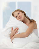 Dreamy beauty girl hugging pillow while in bed Royalty Free Stock Photography