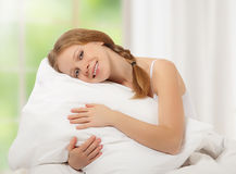 Dreamy beauty girl hugging pillow while in bed Royalty Free Stock Images