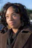 Dreamy black girl otdoors. Portrait of African-American girl in brown coat Royalty Free Stock Image