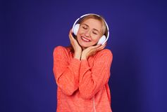 Dreamy blond enjoying good music. Isolated on violet Royalty Free Stock Photo