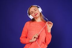 Dreamy blond listening music. On violet Royalty Free Stock Photography