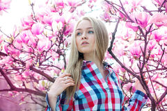 Dreamy blonde girl looking to the side near the spring blooming Stock Photo