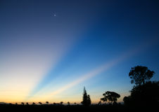 Dreamy blue dusk with sun rays and star. Beautiful blue, gold, pink sky just before dark Stock Photography