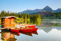 Dreamy boats stand near wooden bridge. Royalty Free Stock Image