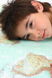 Dreamy boy. Portrait of a boy and a world map as concept for peace, hope and environment protection Royalty Free Stock Image