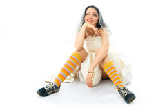 Dreamy bride wearing running shoes and socks. Beautiful dreamy bride wearing old blue running shoes and colorful cocks Royalty Free Stock Image