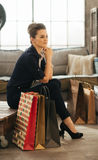 Dreamy brown-haired woman with shopping bags in loft apartment Stock Photo