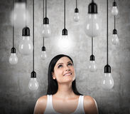 A dreamy brunette looks upward. Lots of light bulbs, one of them is turned on. Stock Photo