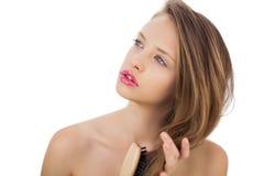 Dreamy brunette model brushing her hair Royalty Free Stock Photography