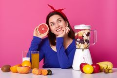 Dreamy cheerful young woman imagines something pleasant, holds fresh grapfruit, makes fresh smoothie, uses blender, sits at white. Desk, isolated over pink royalty free stock photo