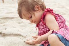Dreamy child. Cute dark-haired kid tiny little child baby girl sitting on haunches and playing with sand on beach on stock image