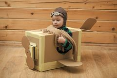 Dreamy child. Brave dreamer boy playing with a cardboard airplane. Dreamy child. Cute dreamer boy playing with a cardboard airplane. Childhood. Fantasy stock photography
