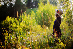 Dreamy child girl on summer walk on riverside. Cozy rural scene. Outdoor activities Royalty Free Stock Photography