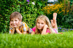 Dreamy children. Happy summer holidays. Two smiling children on a green lawn at a summer park. Happy childhood Royalty Free Stock Photo