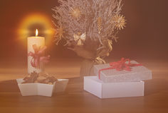 Dreamy Christmas background with snow covered tree, straw decorations, burning candle and open present. Festive background, xmas banner Royalty Free Stock Image