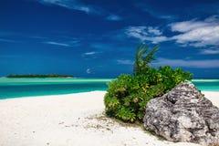 Dreamy clear sea with a rock on the white sandy beach Stock Photos