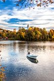 Autumn Landscape with A Lone Boat, Colorful Trees and Houses Reflected in Lake stock image
