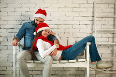 Dreamy couple in red Christmas hats sitting on bench Stock Photography