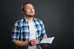 Dreamy creative writer feeling inspired. Looking for inspiration. Enchanting young thoughtful man working on a poem and using his journal for writing it down Royalty Free Stock Photos