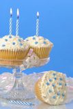 Dreamy Cupcakes. Starry cakes on glass comport with stripy lit candles Royalty Free Stock Image