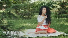 Dreamy curly girl writes poems in park on plaid stock footage