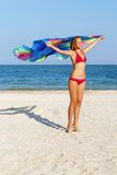Dreamy cute teen girl. Standing on the beach with pareo in hands Stock Image