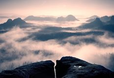Dreamy daybreak on the top of the rocky mountain with the view into misty valley Royalty Free Stock Image