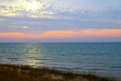A Dreamy Evening at Lake Michigan. This is not your typical sunset sky over Lake Michigan in Covert, Michigan. The pastel yellow sun floats dreamily down to the royalty free stock photos