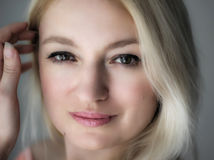 Dreamy eyes. Blond woman smiling portrait close up royalty free stock image