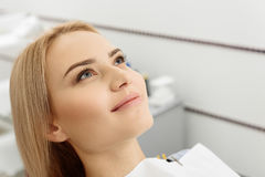 Dreamy eyes and cute smile of woman at stomatology. Close up pretty patient with brooding eyes in dental office waiting when anesthesia starting to act Stock Image