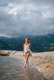 Dreamy fashion girl walk on beach with mountains background Royalty Free Stock Photos