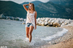 Dreamy fashion girl walk on beach with mountains background Royalty Free Stock Photo