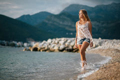 Dreamy fashion girl walk on beach with mountains background Royalty Free Stock Images