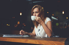 Dreamy female enjoying cup of tea while sitting in cozy coffee shop during her recreation time Royalty Free Stock Photo