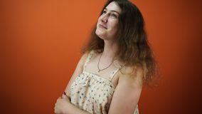 The dreamy woman was thinking about something, on an orange background. The dreamy female was thinking about something, on an orange background stock footage