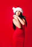Dreamy girl. Beautiful dreamy brunette girl wearing a Santa's hat against red background Royalty Free Stock Photo
