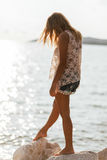 Dreamy girl on beach with light breeze winfd in hair Royalty Free Stock Image
