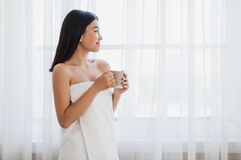 Dreamy girl with cup of morning coffee looking through window