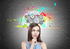 Dreamy girl in a dress, brain cogs. Portrait of a dreamy teen girl wearing a blue dress and holding her hands near the face. She is standing near a blackboard Royalty Free Stock Images
