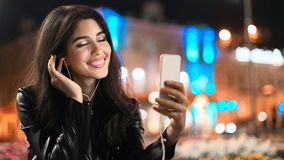 Dreamy girl enjoying song on phone in city, copy space stock photo