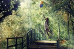 A dreamy girl in a forest with balloons. royalty free stock images