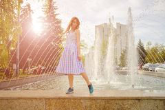 Dreamy girl by fountain. Dreamy girl in summer blouse and fluffy skirt with colorful dots walking by the fountain carefree. Romantic curly-haired girl walking Stock Photos