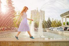 Dreamy girl by fountain. Dreamy girl in summer blouse and fluffy skirt with colorful dots walking by the fountain carefree. Romantic curly-haired girl walking Royalty Free Stock Images